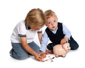 Brothers filling their piggy bank — Stock Photo
