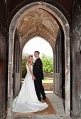 Wedding couple in church entrance — Stock Photo