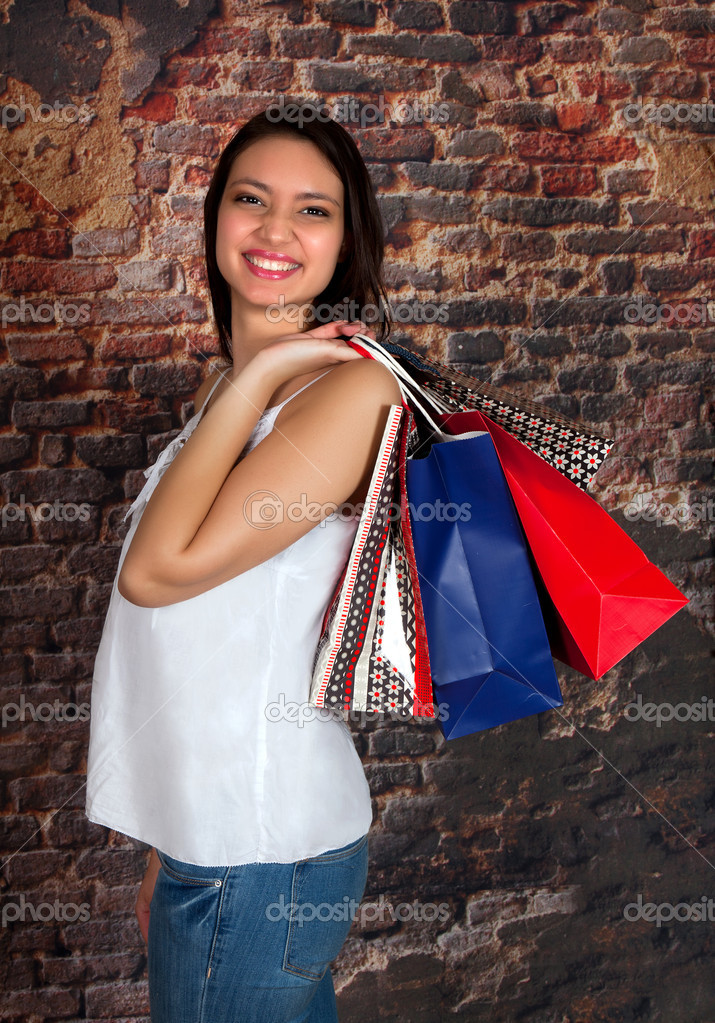 Young smiling happy woman with shopping bags in her hand — Stock Photo #9558191