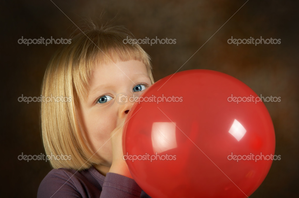 Little girl blowing a red balloon for her birthday party  Stock Photo #9721730