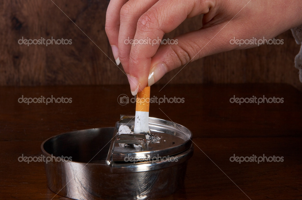 Hand finishing a cigarette in an ashtray — Stock Photo #9805592