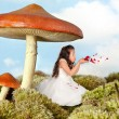 Fairy girl blowing rose petals — Stock Photo