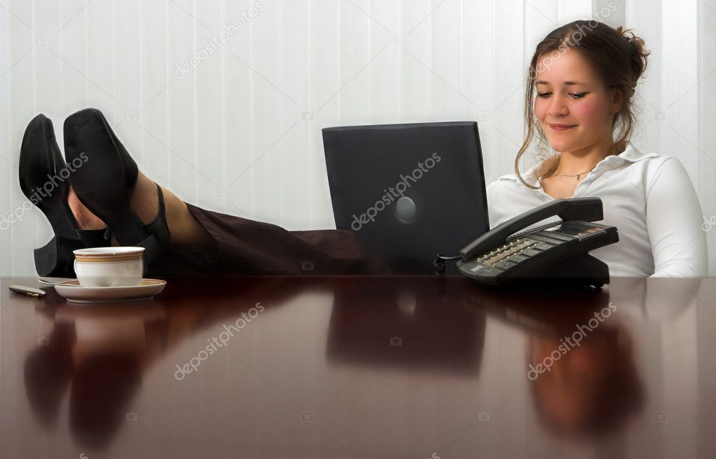 Young woman with laptop in meeting room, with her feet on the table — Stock Photo #9990859