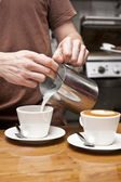 Barista pouring milk — Stock Photo