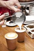 Barista pouring milk — Stock Photo
