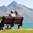 Foto Stock: Rear view of senior couple sitting on park bench