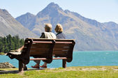 Rear view of a senior couple sitting on a park bench — Stock Photo