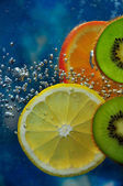 Two kiwi fruit, lemon and orange — Stock Photo