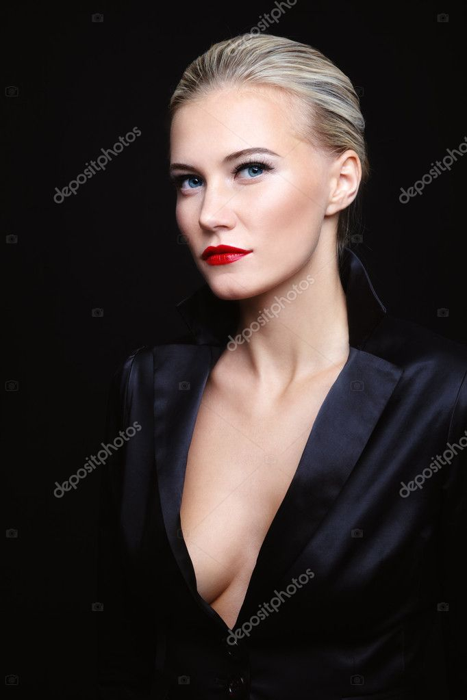 Young beautiful blond glamorous woman in black silky jacket over dark background  Stock Photo #8631577