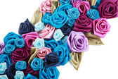 Blue, vinous, pink and turquois handmade silk roses on white background — Stock Photo