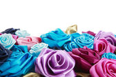 Blue, vinous, pink and turquois handmade silk roses on white background — Photo