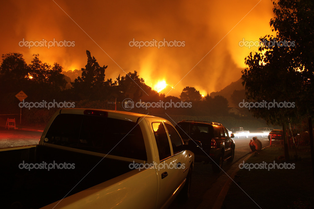 Residents of a neighborhood sit by and watch a fire threaten their homes.  Stock Photo #8655735