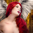 Beautiful gothic sexy angel with wings, red hair over gold backg — Stock Photo