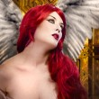 Stock Photo: Beautiful gothic sexy angel with wings, red hair over gold backg