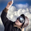 Boy as an old style pilot holding a toy airplane, heaven backgro — Stock Photo