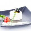 Vanilla mousse dessert on square black plate with cranberries - Stock Photo