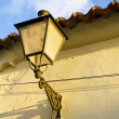 Stock Photo: Street light on stone wall, spain.