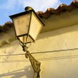 Street light on stone wall, spain. - Stock Photo