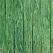 Green paint peeling from a wooden panel door. Aged texture — Stock Photo