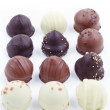 Delicious dark, milk, and white chocolate truffles. - Stock Photo