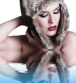 Sexy winter woman with reflection in water, on white background. — Stock Photo
