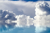 A sky of clouds reflected in a calm sea. — Stock Photo