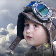 A little cute baby dreams of becoming a pilot. Pilot outfit, hat — Stock Photo #10398781