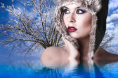 Winter woman with snow hat and intense red lips reflected in a c — Stock Photo