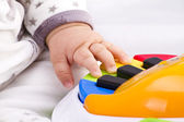 Little baby hand pianist plays on a colorful toy piano — Stock Photo