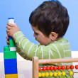 Baby is playing with educational toys over wooden background — Stock Photo #10418413