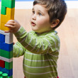 Cute little brunette baby playing with colorful blocks — Stock Photo