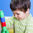 Brunette Baby playing with bright blocks on wooden room — Stock Photo
