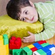 Cute little brunette child is playing with toys while sitting on — Stock Photo