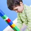 A smiling little boy is building a toy block. Wooden room — Foto Stock