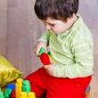 A happy little boy is building a colorful toy block tower — Stock Photo