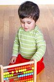 Bebé caucásico en camiseta verde jugando con el bloque de colorido brillante — Foto de Stock