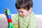 Brunette bébé jouer avec des blocs lumineux sur la pièce en bois — Photo