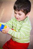 Lindo niño poco morena está jugando con juguetes mientras está sentado en — Foto de Stock