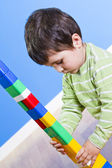 A smiling little boy is building a toy block. Wooden room — Stock Photo