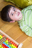 Happy little boy playing with colorful abacus, studio shot — Stock Photo