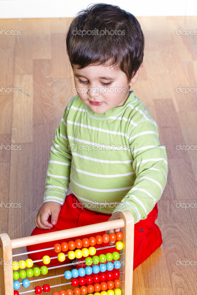 Caucasian baby in green shirt playing with bright colorful blocks — Stock Photo #10418418