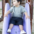 Caucasian baby boy playing on sliding board - Stock Photo