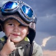Adorable baby dressed in pilot uniform with funny face — Stock Photo #10687615