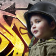 Stock Photo: Baby playing war with military helmet against graffiti backgroun