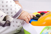 Newborn baby boy playing with a toy piano — Stock Photo