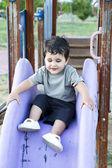 Söt baby spelar på glidande styrelse, leende — Stockfoto