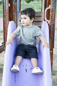 Cute baby playing on sliding board — Stock Photo
