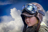 Child pilot, cute and funny over background clouds — Stock Photo