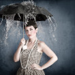 Pin-up girl with umbrella under water splash — Stock Photo #8661589