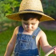 Little baby boy gardener watering the grass in serious fashion — Stock Photo #8663321